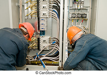 Electricians at work - Two electricians working on a...