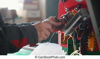 Electrician's hands installing energy system on machinery...
