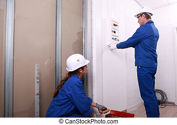 Electricians installing a distribution board