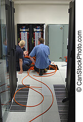 Electricians - Two electricians install additional power...