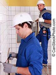 Electricians wiring a bathroom