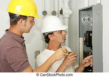 Electricians wiring an electrical breaker panel. Models are professional electricians - all work depicted is being performed according to industry codes and safety standards.