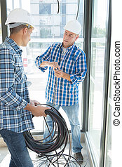 electricians with construction tools and cable
