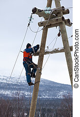 Electricians working on a pole in winter