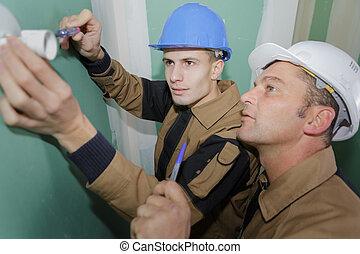electricista, con, aprendiz, trabajando, en, nuevo hogar