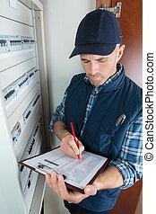 electricista, trabajador, verificar, portapapeles, mientras, trabajando, en, fuse-board