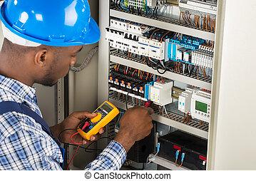 electricista, verificar, cajade fusibles, con, multímetro