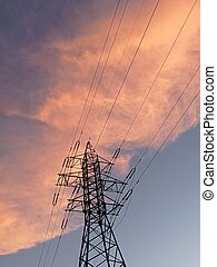 Electricity distribution station.Silhouette high voltage electric towers at sunset time. High-voltage power lines
