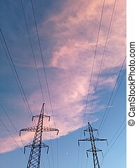 Electricity distribution station.Silhouette high voltage electric towers at sunset time. High-voltage power lines.Moon