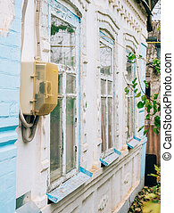 Electricity meter on the building. Old white-washed house in the