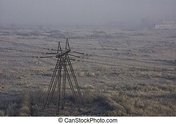 Electricity post with cable lines in the morning mist