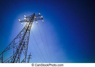 electricity pylon against blue sky with sun - a power mast...