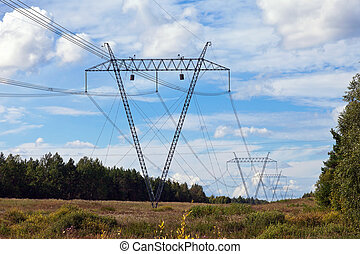 Electricity pylon on a background of blue sky with clouds