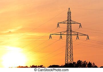 electricity pylon against orange sunset
