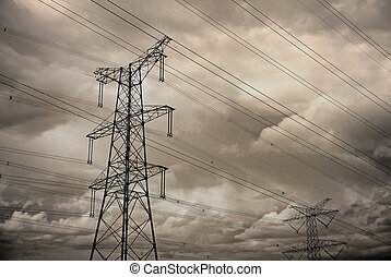 Electricity pylon with many cables on cloudy moody sky
