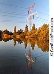 Electricity pylon with reflection in water