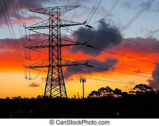 Electricity pylons and communication tower at sunset