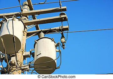 Close up of electricity transformers up in power line post, against blue sky.