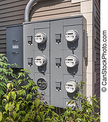 Electricity usage meters - electric meters on the side of a...