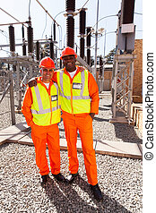 electricity workers standing in electrical substation