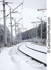 Electrified railway line with poles for wires at winter ...