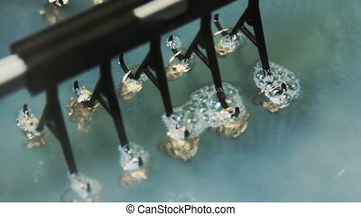 Electrochemical treatment of gold jewelry.