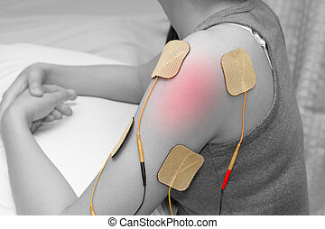 electrodes of tens device on shoulder, tens therapy, nerve stimulation for release pain