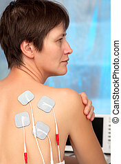 electrodes of tens device on the woman's back, tens therapy, nerve stimulation