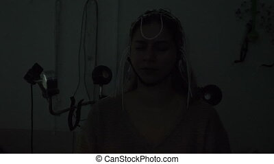 Electroencephalographic examination in clinic. Equipment for receiving brain EEG human. Female patient wired to EEG machine or electroencephalograph which produces graphical record of brain electrical activity. 4 k