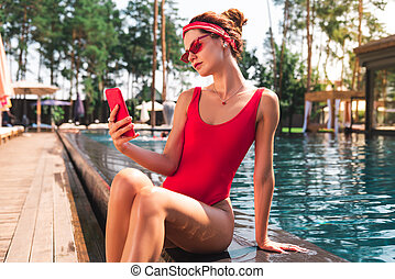 Nice pleasant young woman using her modern smartphone