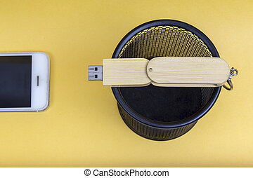 Electronic equipments in trash can on yellow background
