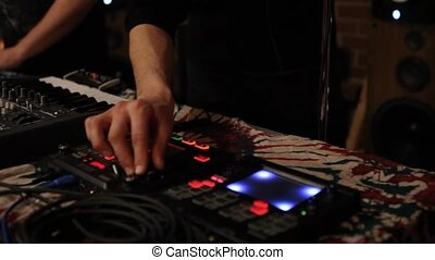 Hands of young deejays are seen up-close, playing a live music set together inside a modern nightclub. Entertainment and nightlife.