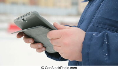 Electronic pad in male hands against building construction