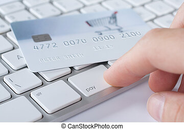 On-line payment concept (e-banking). Keyboard with button pay and credit card with shopping cart on the photo. I am author of photo used on credit card and used data are fictitious.