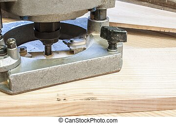 Electronic Plunge Router with pine wood planks, construction background