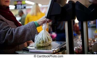 Electronic scales in the supermarket, customer - old woman - weighs the grapes in vegetable department