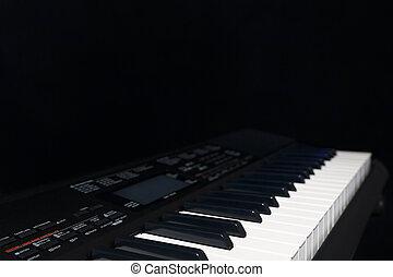 Electronic synthesizer on black background