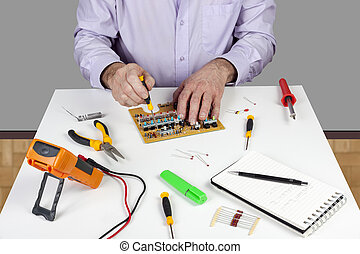 Electronic test engineer using a screwdriver to mount a circuit board switch