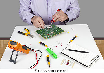 Electronic test engineer using a soldering iron on a printed circuit board