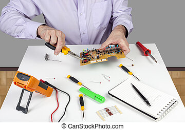Electronic test engineer using long nose pliers mount component in a circuit board