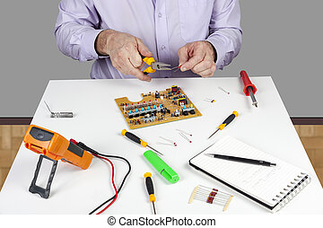 Electronic test engineer using long nose pliers to form a circuit board component