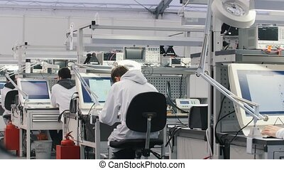 Electronics engineers working in lab. Engineers sitting at the table and working on the computer