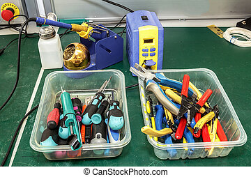 electronics equipment assembly workplace with pliers and ...