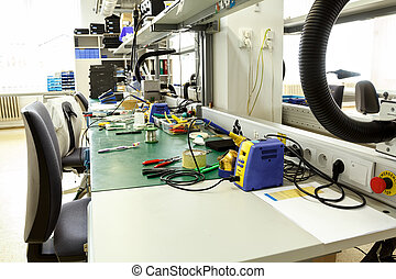 electronics equipment assembly workplace with pliers and...