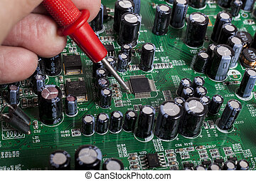 Electronics Repair service close-up with red probe and ...