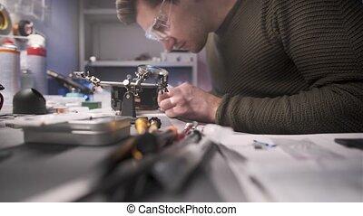 Electronics repairman master repairs smartphone in service center.