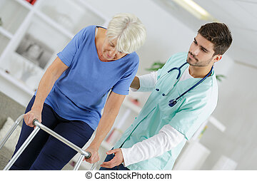 eledely lady using walking frame with help of caregiver