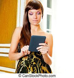 elegance fashion woman reading ebook tablet in a door