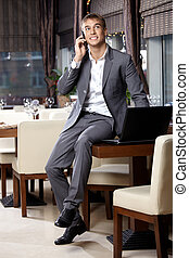 Elegance - Happy business man speaks by a mobile phone at...