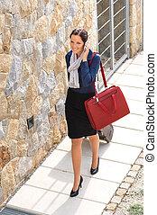 Elegance woman leaving home luggage calling phone